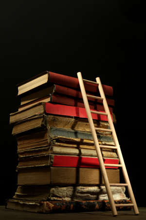 Old books and wooden ladder, on black background photo