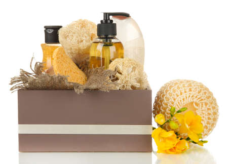 Composition of cosmetic bottles and soap in crate, isolated on white photo