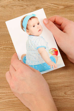 Photos in hands on wooden table Stock Photo - 19360013