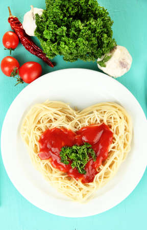 Cooked spaghetti carefully arranged in  heart shape and topped with tomato sauce, on  blue background photo