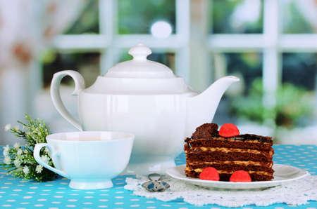 decoracion de pasteles: Tetera, taza de té y delicioso pastel en fondo de la ventana Foto de archivo