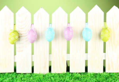 Art Easter background with eggs hanging on fence photo