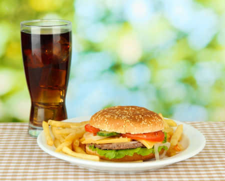 Tasty cheeseburger with fried potatoes and cold drink, on bright background photo