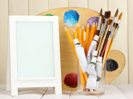 Photo frame as easel with artist's tools on wooden background photo