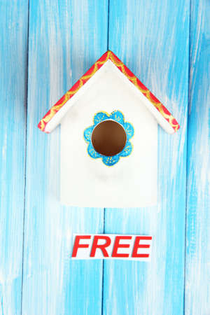 Decorative nesting box and sign on color background photo
