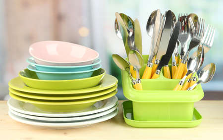 Plates, forks, knives, spoons and other kitchen utensil on bright background Stock Photo - 18685879