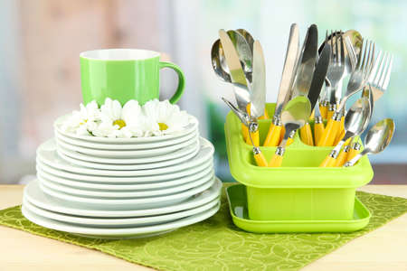Plates, forks, knives, spoons and other kitchen utensil on color napkin, on bright background photo