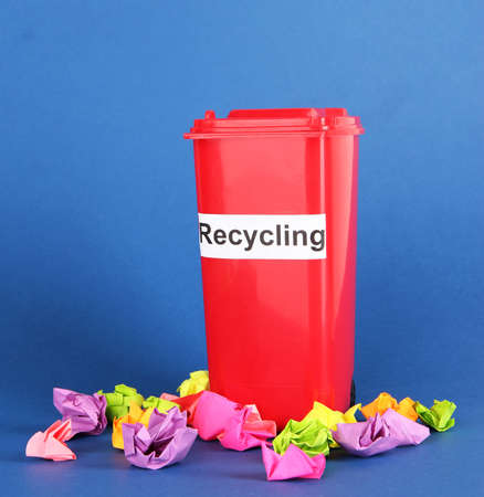 Recycling bin with papers on blue background photo