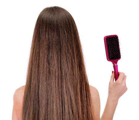 back straight: Portrait of beautiful woman with long hair and a hairbrush, isolated on white