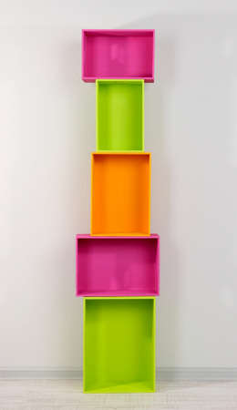 Beautiful colorful crates as shelves standing in room photo