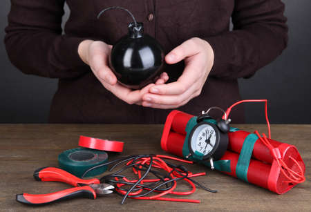 Human makes timebomb on wooden table on black background Stock Photo - 18695314