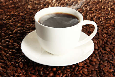 Cup of coffee on coffee beans background photo