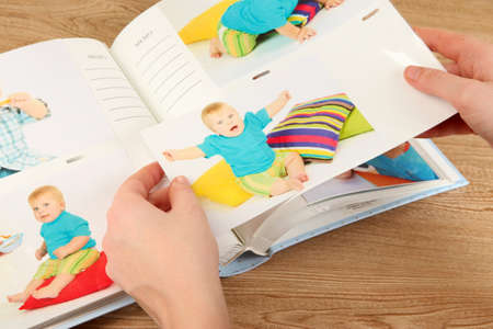 Photos in hands and photo album on wooden table Stock Photo - 18695364