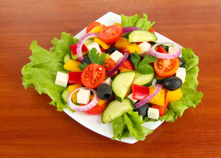 Tasty Greek salad on wooden background photo