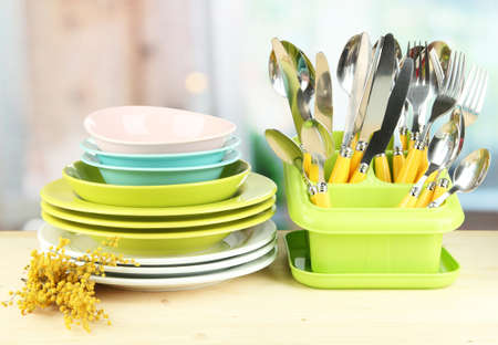 Plates, forks, knives, spoons and other kitchen utensil on bright background photo