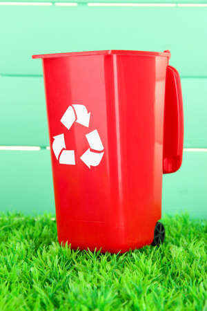 degradable: Recycling bin on grass on light blue background