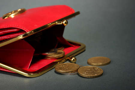 takings: female red wallet with coins on grey background