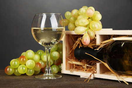 Wooden case with wine bottle, wineglass and grape on wooden table on grey background Stock Photo - 18717790