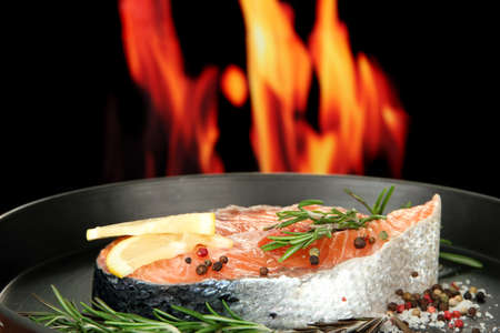 Fresh salmon steak on pan, on fire background, close up photo