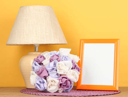 Colorful photo frame, lamp and flowers on wooden table on yellow background