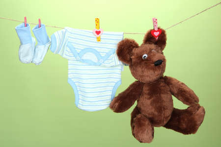 Baby clothes hanging on clothesline, on green background photo