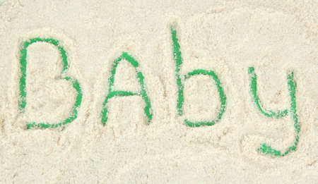 Word baby making with powdered milk on green background photo