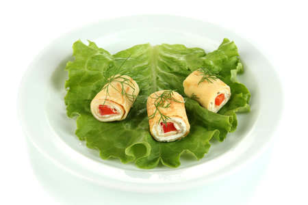 Egg rolls with cheese cream and paprika, on  green salad leaves, isolated on white photo