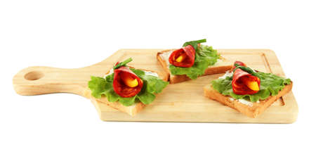 Salami rolls with paprika pieces inside, on  roasted bread, on wooden board, isolated on white Stock Photo - 18715979