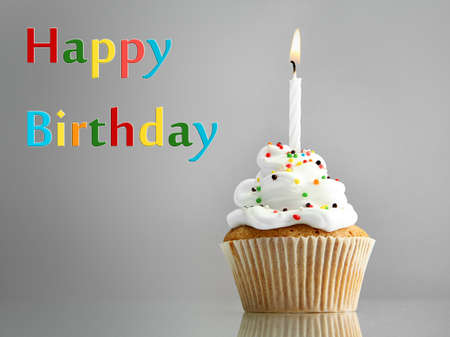 Tasty birthday cupcake with candle, on grey background photo