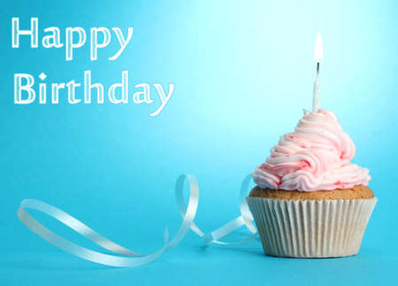 tasty birthday cupcake with candle, on blue background photo