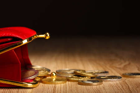 economise: female red wallet with coins on wooden table, on black background Stock Photo