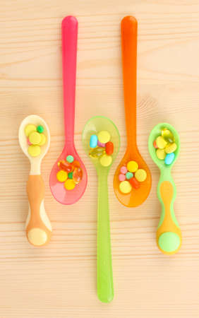 Plastic spoons with color pills on wooden background photo