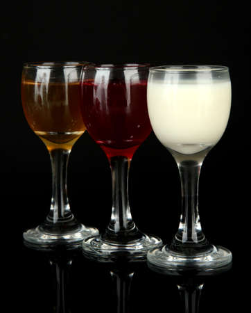 Tasty color liquors, isolated on black photo