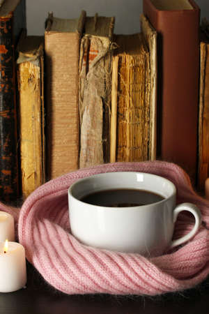 Cup of coffee wrapped in scarf on books background photo