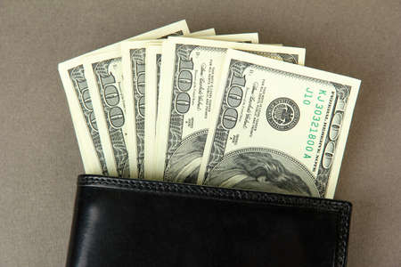 Wallet with hundred dollar banknotes, on color background photo