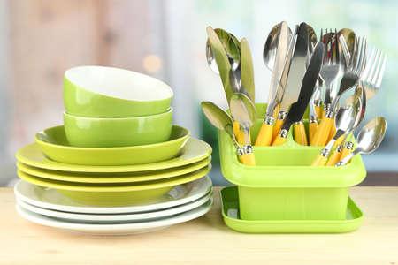 kitchen utensils: Platos, tenedores, cuchillos, cucharas y otros utensilios de cocina sobre fondo brillante