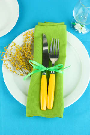Knife and fork wrapped in napkin, on plate, on color tablecloth  background Stock Photo - 18742157