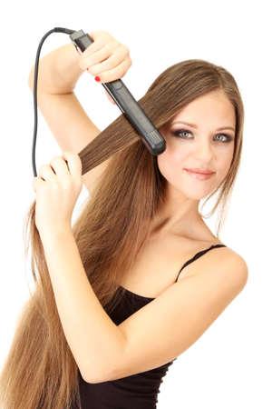 Donna che fa acconciatura con il raddrizzatore dei capelli, isolato su bianco Archivio Fotografico