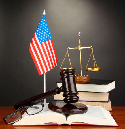 Wooden gavel, golden scales of justice  and books on grey background photo