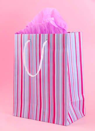 Striped shopping bag on pink background photo