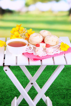 Beautiful composition with cup of tea and marshmallow on wooden picnic table on natural background photo