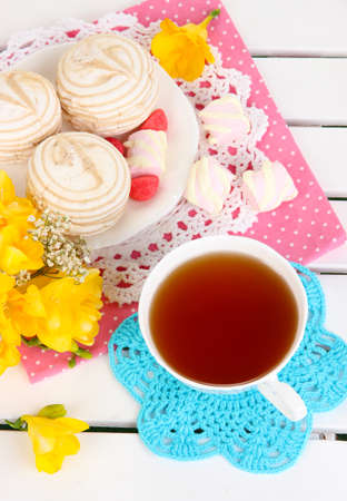 Beautiful composition with cup of tea and marshmallow on wooden picnic table close-up photo