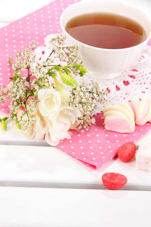 Beautiful composition with cup of tea and flowers on wooden picnic table close-up photo