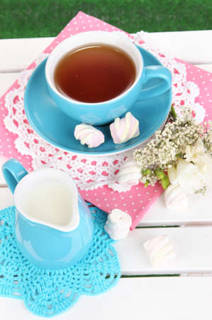 Beautiful tea composition on wooden picnic table close-up photo