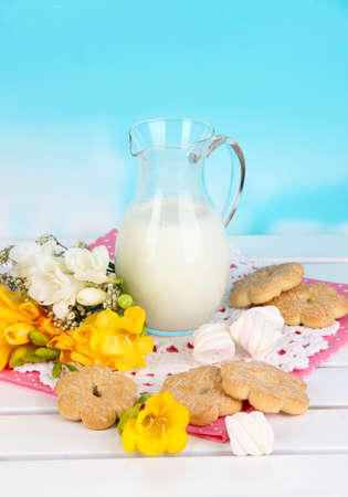 Beautiful composition of milk and cookies on wooden picnic table on natural background photo