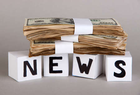 White paper cubes labeled News with money on grey background