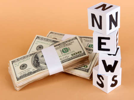 White paper cubes labeled News with money on beige background
