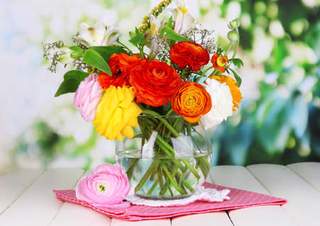 flower vase: Excellent buttercup flowers in glass vase on wooden table on natural background