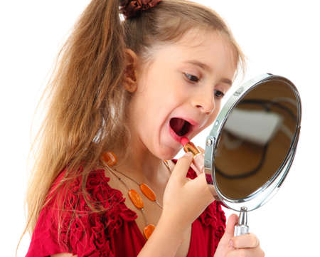 little girl in her mother's dress, is trying painting her lips, isolated on white Stock Photo - 19360429