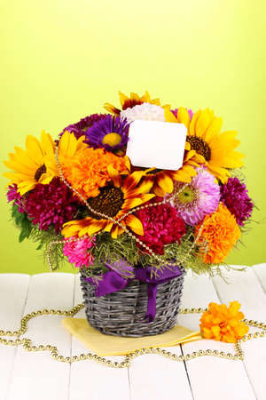 ronantic: Beautiful bouquet of bright flowers with paper note on wooden table on green background